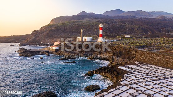 View of coastline with lighthouse and salt flats at sunset