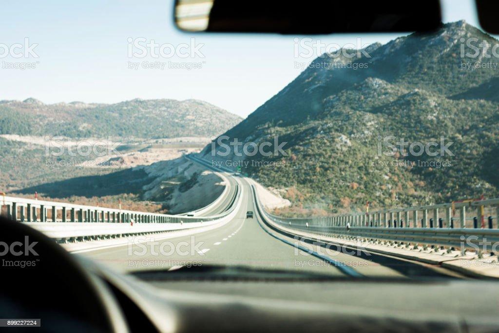 Ansicht des Cockpits von Auto fahren zu einer langen Autobahn am Berg – Foto