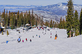 View of Snowmass Mountain slope in the winter; skiers ski down the slope