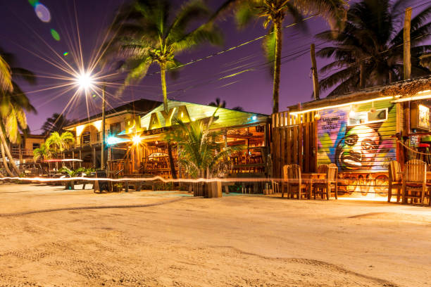 A view of colorful restaurants on Ambergris Caye island beach at dusk.