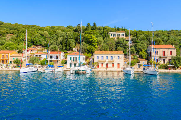View of colourful houses and sailing boats in Kioni port on Ithaca island, Greece Kefalonia is a Greek island in Ionian Sea. It is the largest of Ionian islands and the sixth largest Greek island. sailing dinghy stock pictures, royalty-free photos & images