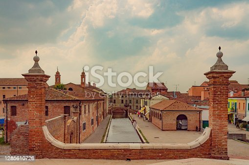 View of Comacchio canal and colorful houses against cloudy sky