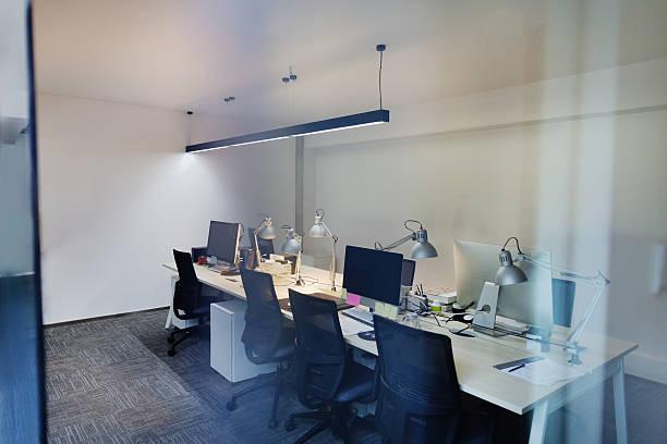 view of computer design studio office through glass wall - oficina de empleo fotografías e imágenes de stock