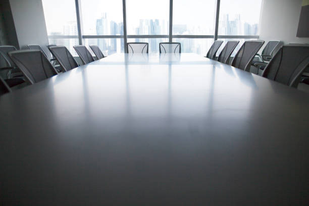 View of conference room table and chairs Low angle view of contemporary conference room table and chairs in urban city environment downtown skyscraper high rise above symmetry balance scale governing board stock pictures, royalty-free photos & images
