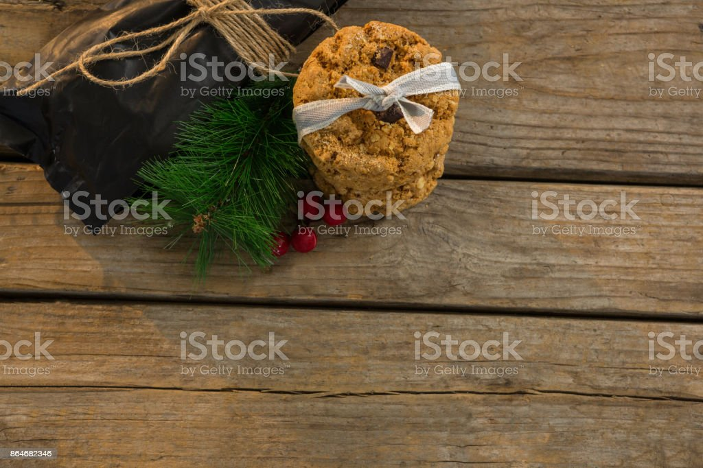 View of cookies with pine needles and cheeries by plastic bag on table stock photo
