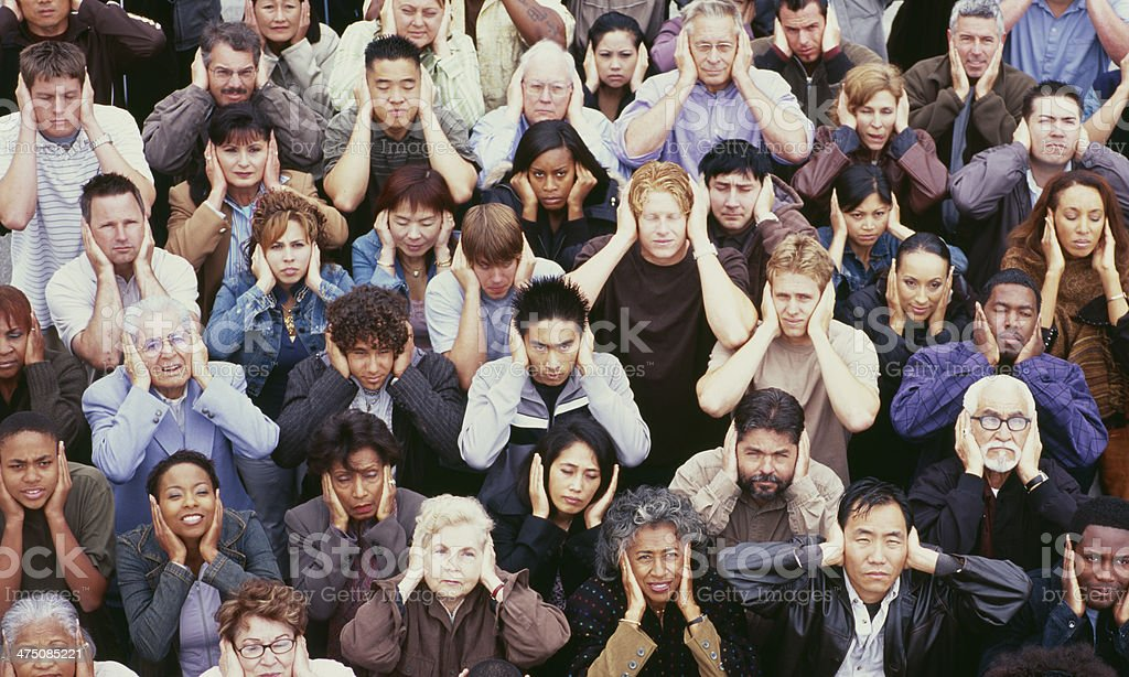 View of crowd covering ears stock photo