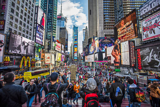 view of crowded times square in new york city - times square stock photos and pictures