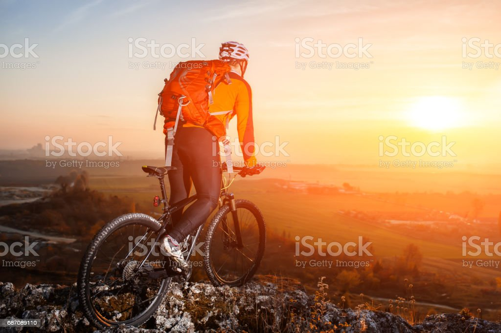 View of cyclist standing with mountain bike on hill trail at sunset Lizenzfreies stock-foto