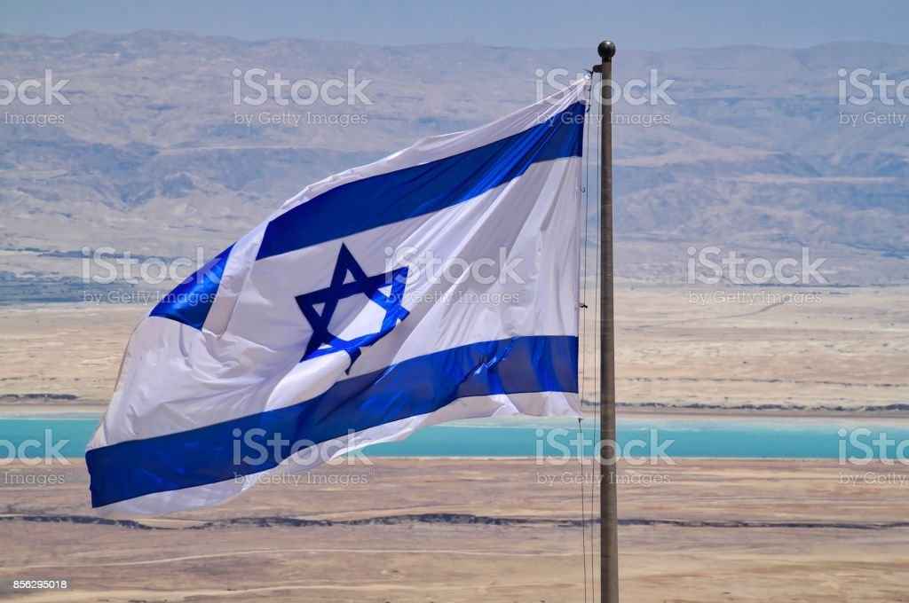 View of Dead Sea and Jordanian mountains in background with Israeli flag seen in foreground, seen from Masada stock photo