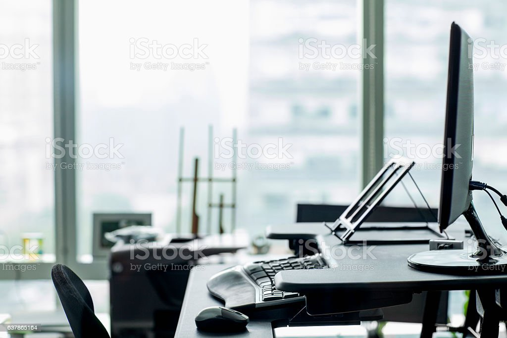 View of desk and computer in technology office stock photo