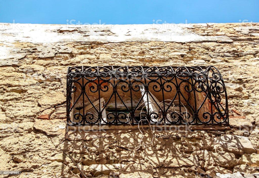 Vista de detalle del edificio de piedra con estilo árabe Mediterráneo típico de ventana y balcón con forja antigua adorno Medina de Túnez, Túnez / Túnez decoraciones de ventana / un azul cielo de fondo. - foto de stock