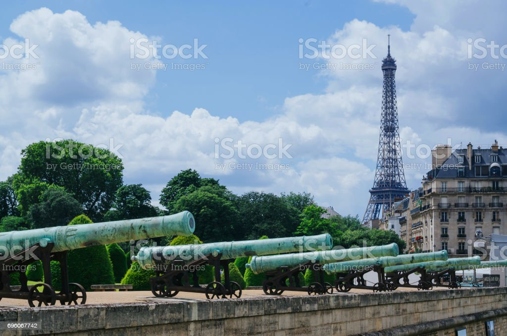 View of Eiffel tower with old cannons of military museum at Les Invalides esplanade in foreground, Paris, France. stock photo