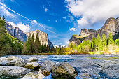 Landscape image of El Capitan and Half Dome in Yosemite National Park with the rocky shore of the Merced River in the foreground, with a vibrant blue cloudy sky.