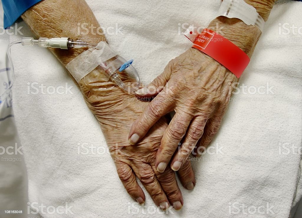 """View of elderly womans hands with IVs and hospital bracelets Hands of an elderly woman in the hospital with an IV and allergy band. I'm honored that this image was used in istockphoto's book """"Parallel Perspectives"""". Vertical image. 70-79 Years Stock Photo"""