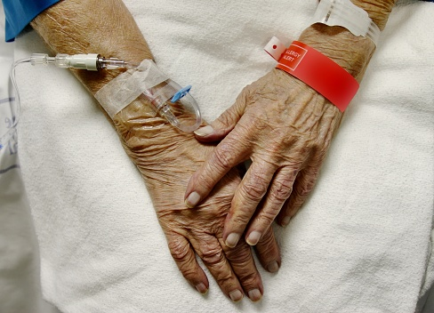View Of Elderly Womans Hands With Ivs And Hospital Bracelets Stock Photo - Download Image Now