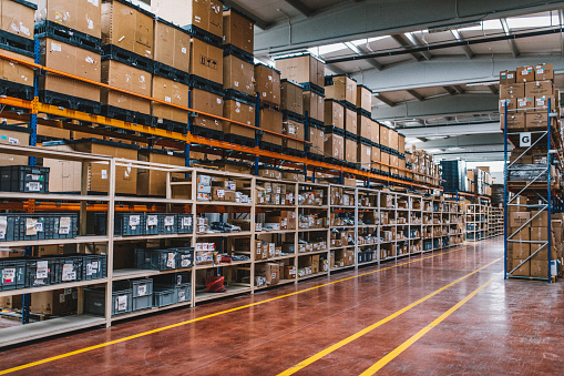 Rows of many shelves with cardboard boxes in storage room of huge distribution warehouse aisle in industrial storage factory background XXXL size