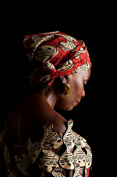3/4 view of expressive African female in traditional dress/looking down stock photo