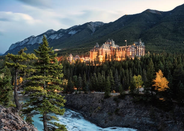 View of Fairmont banff springs luxury hotel with illumination in valley and river at National Park stock photo