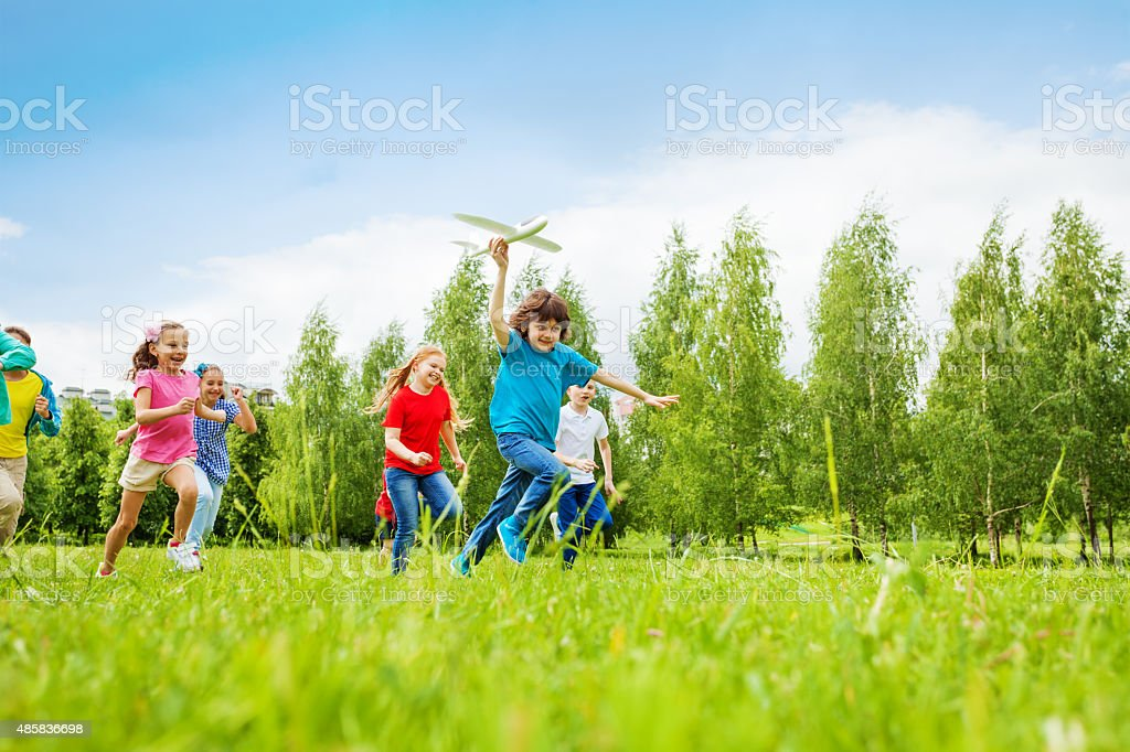 View of fast moving boy holding white airplane toy stock photo