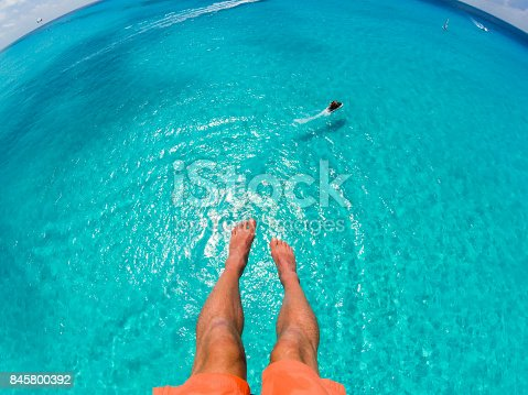 istock View of feet parasailing with the speed boat in the sea background 845800392