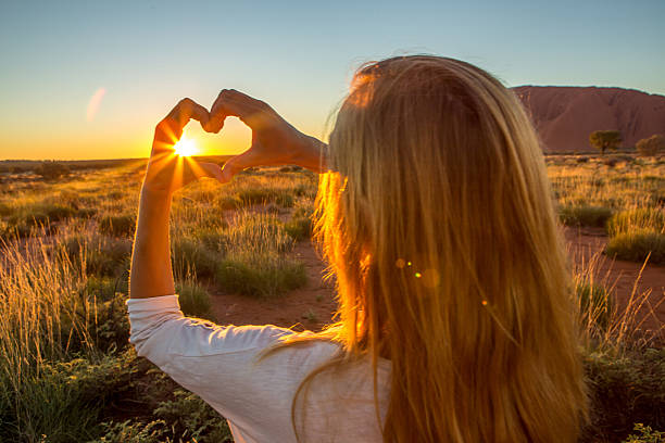 View of female framing sunset into heart shape stock photo