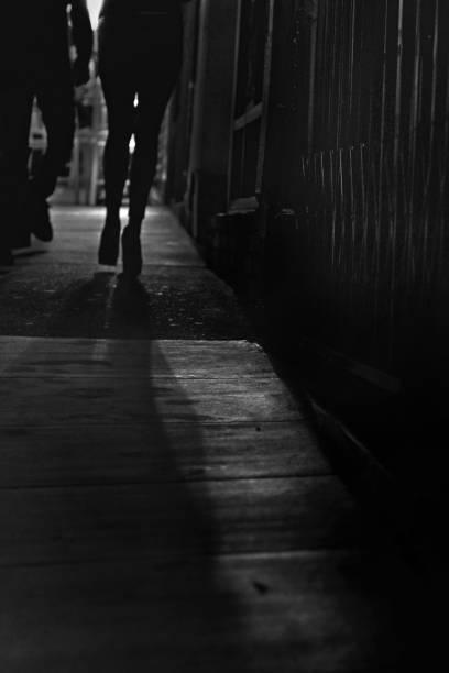 blick auf weibliche beine silhouette auf fersen auf der straße - pimp stock-fotos und bilder