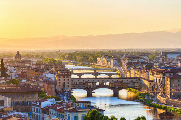 View of Florence at sunset with the Ponte Vecchio Bridge and the Arno River View of Florence at sunset with the Ponte Vecchio Bridge and the Arno River florence italy stock pictures, royalty-free photos & images