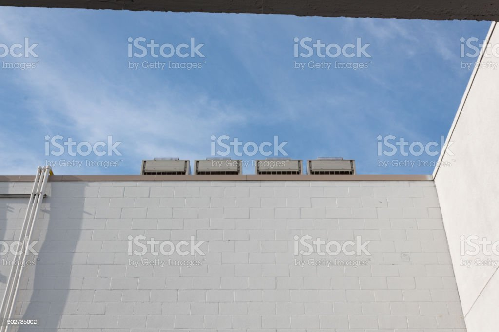 View of four cooling units on top of a white block building against a blue sky, copy space stock photo