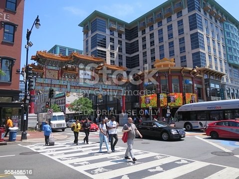View of pedestrians crossing the street and walking on the sidewalks near the Friendship Archway in Chinatown, Washington DC, located at the intersection of 7th and H Street NW, on a sunny day in May 2018