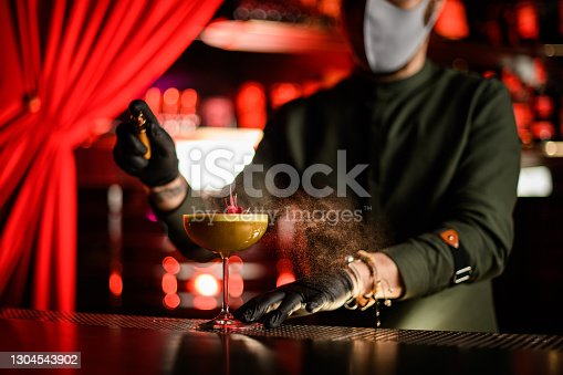 beautiful view of glass with alcoholic cocktail decorated with flower on which man bartender sprinkles