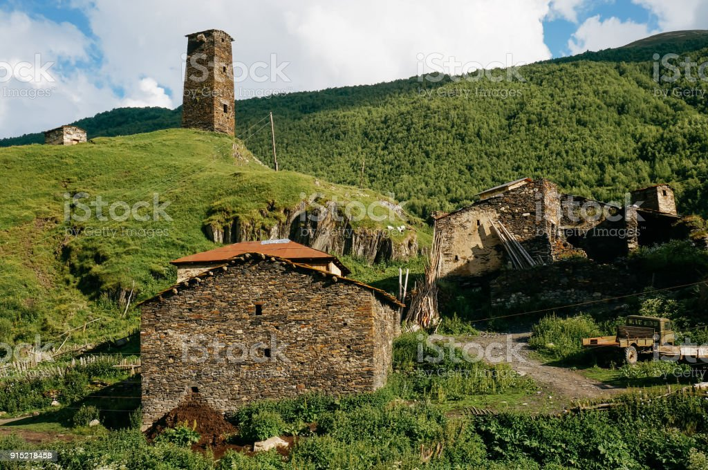 view of grassy field with old weathered rural buildings and hills on background, Ushguli, svaneti, georgia stock photo