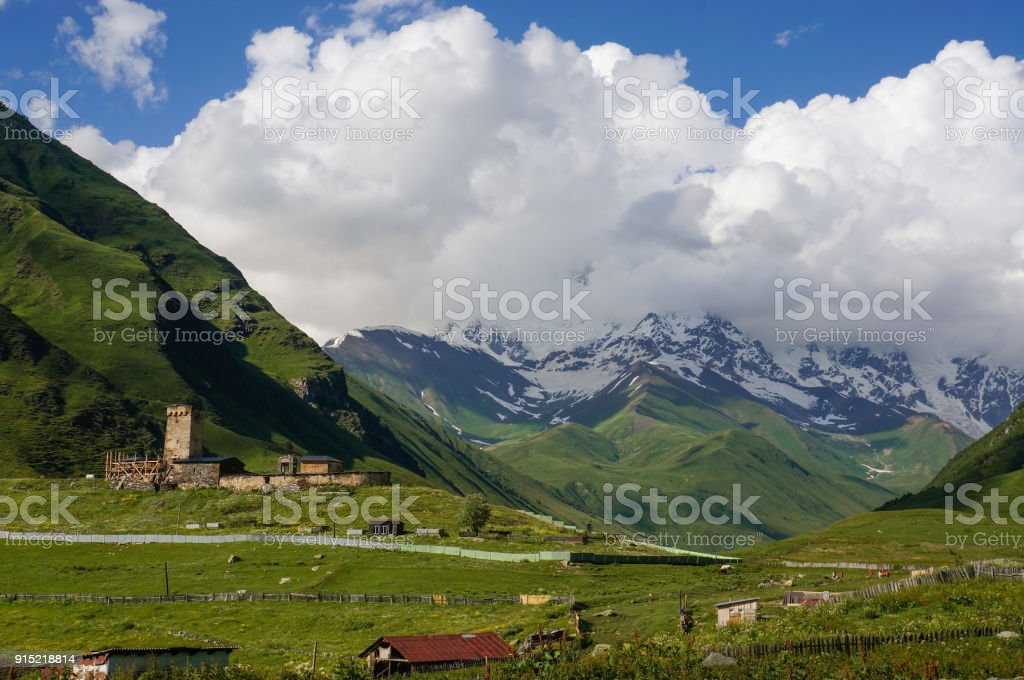 view of green grass meadow with houses and buildings and mountains on  background, Ushguli, svaneti, georgia stock photo
