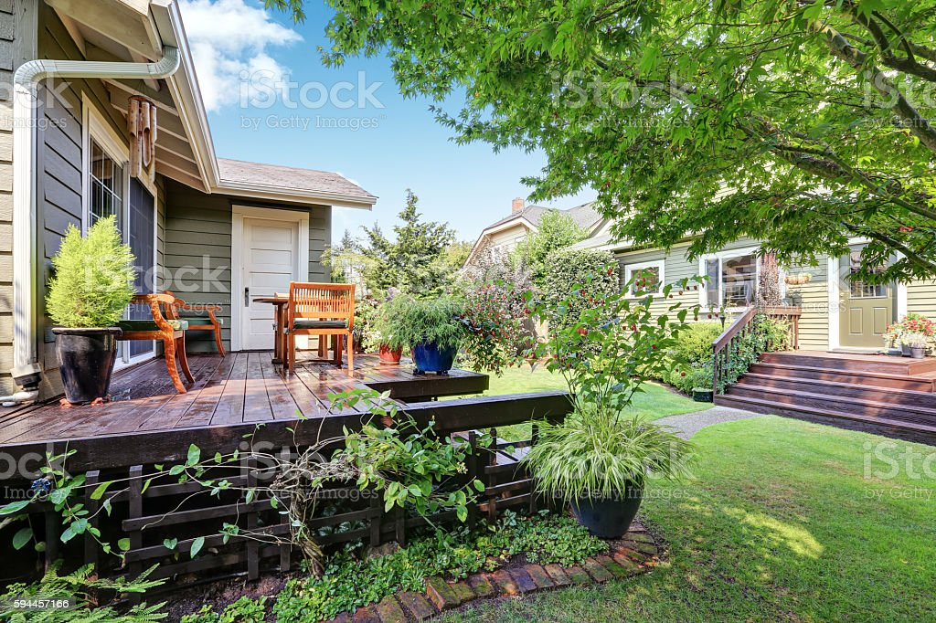 View of guest house with wooden deck and trimmed garden stock photo