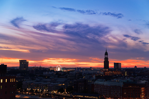 View of Hamburg's landmarks at sunset - Dancing towers, Ferris Wheel and St. Michaelis church