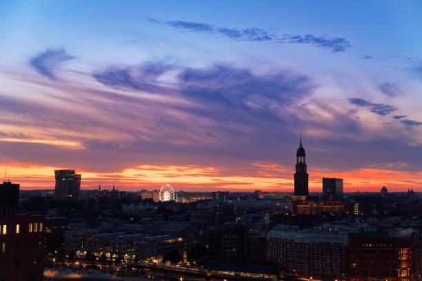 View of Hamburg's landmarks at sunset - Dancing towers, Ferris Wheel and St. Michaelis church stock photo