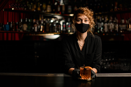 view of handsome young woman in black mask and black gloves who stands behind the bar and holds glass with cocktail