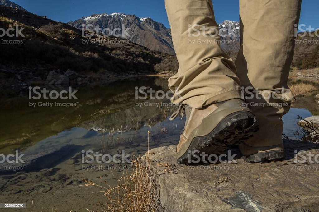View of Hiker's boots standing on rock by the lake stock photo