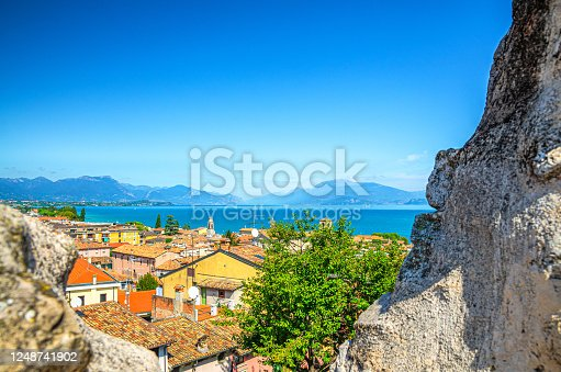View of historical centre Desenzano del Garda old town, lake and mountain range through merlons of brick stone ruined wall of medieval castle, blue sky copy space, Lombardy, Northern Italy