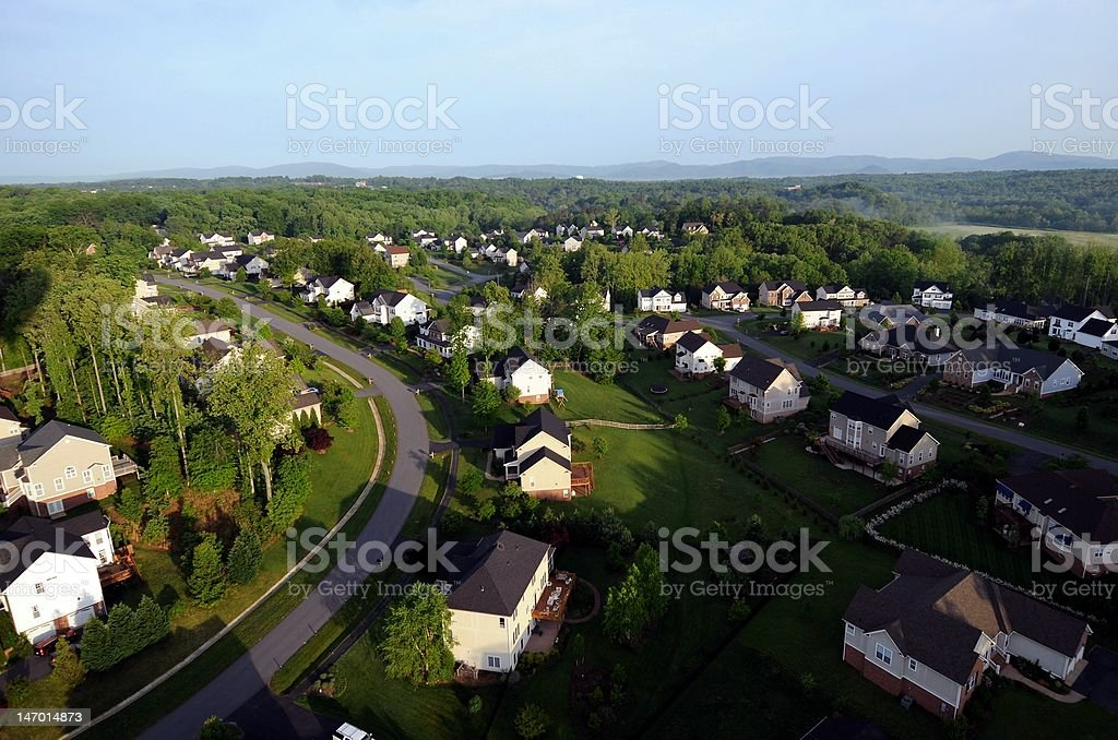 View of Homes and Neighborhoods from the Air Photo taken from hot air balloon of homes and neigborhoods.  Photo features a road, several homes, yards and a neighborhood.  In the background, there are mountains and expansive views of trees. Aerial View Stock Photo