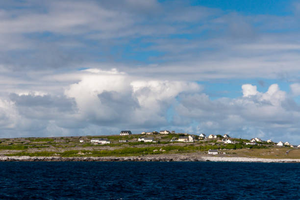 View of Inisheer from Doolin Ferry Looking west toward Inisheer after the Doolin Ferry to Inisheer passes the Plassey wreck.  View of a place named Sheeaunroe from the ferry deck.  Inisheer, Aran Islands, County Galway, Republic of Ireland michael stephen wills aran stock pictures, royalty-free photos & images