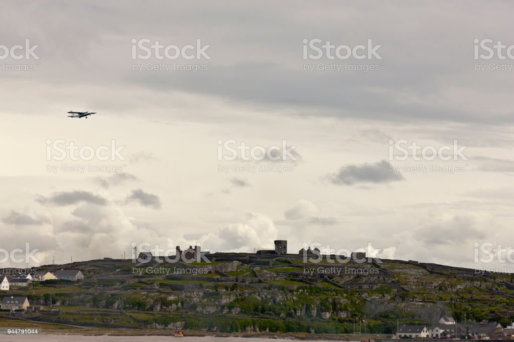 View of Inisheer from Doolin Ferry with O'Brian's Castle, airplane and bonfire. stock photo