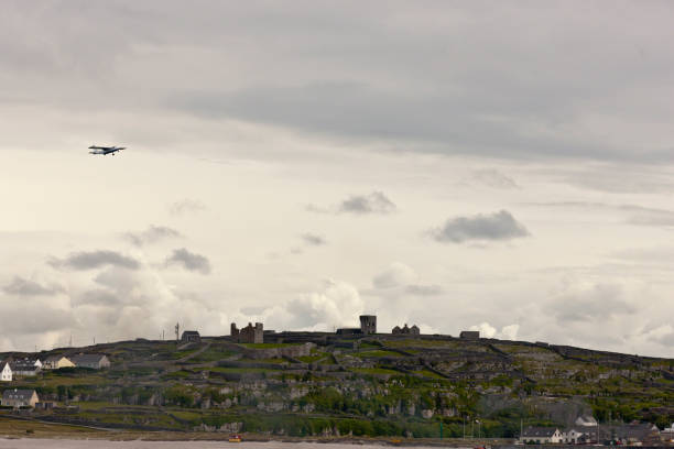 View of Inisheer from Doolin Ferry with O'Brian's Castle, airplane and bonfire. Looking southwest toward Inisheer as the Doolin Ferry approaches the dock at Caherard.  O'Brian's Castle on the hill summit.  On upper left, a small airplane taking off from the island airport.  There is smoke from a small bonfire at lower right near the ferry dock. michael stephen wills aran stock pictures, royalty-free photos & images