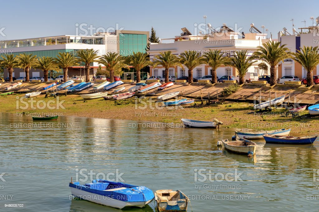 View of Isla Cristina in Southern Spain, with colorful boats and palm trees on the shore. stock photo
