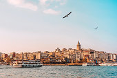 View of Istanbul cityscape Galata Tower with floating tourist boats in Bosphorus ,Istanbul Turkey