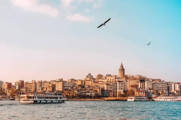 вид на стамбульский городской пейзаж галата башня с плавучими туристическими лодками в босфоре , стамбул турция - стамбул стоковые фото и изображения