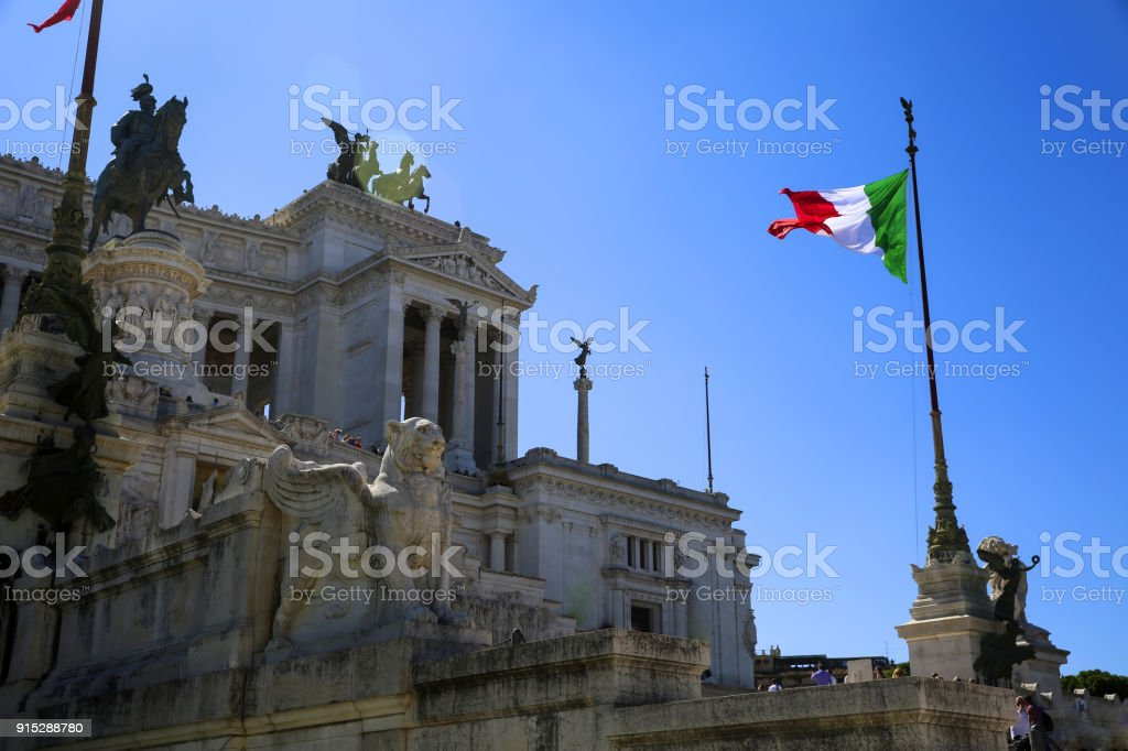 View of Italian national flag in front of Altare della Patria (Altar of the Fatherland) , the equestrian sculpture of Victor Emmanuel stock photo