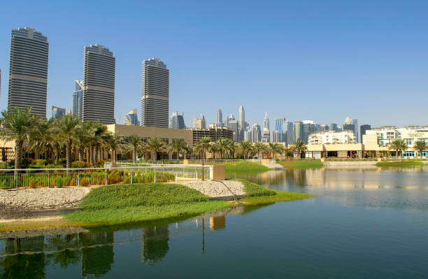 View of Jumeirah Islands housing development promenade with JLT skyscrapers as a background and  artificial lake with a park stock photo