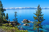 Mother wake surfs behind a boat on beautiful Lake Tahoe, California.