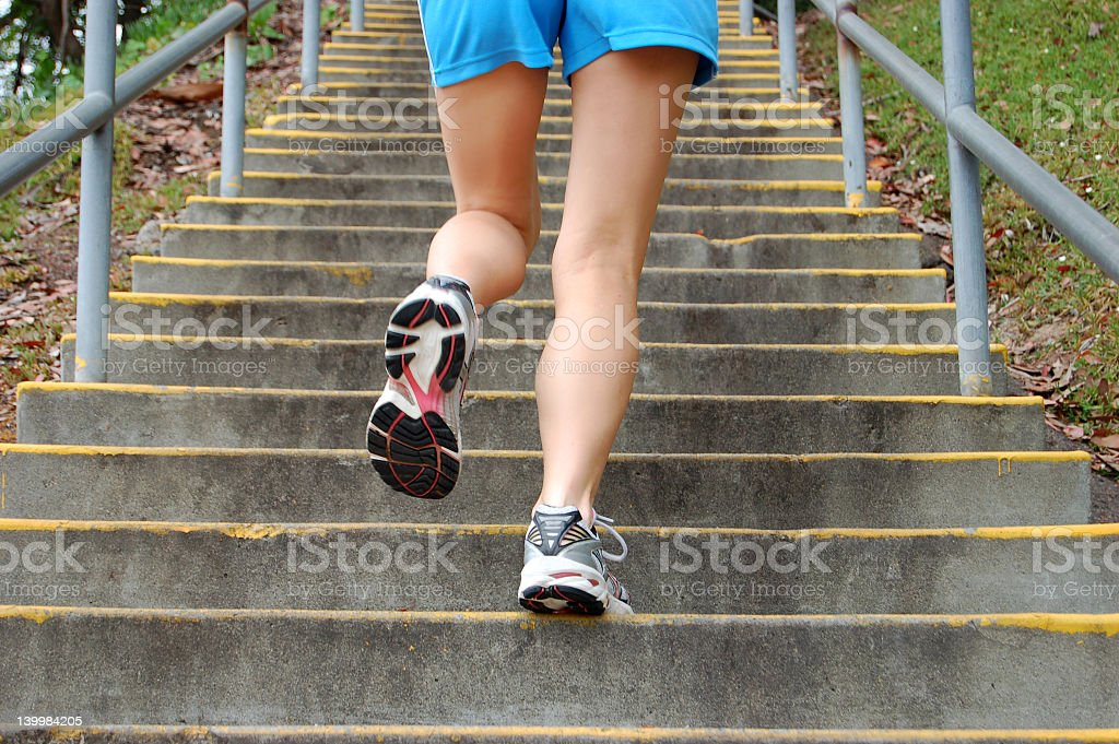 View of legs climbing outdoor steps stock photo