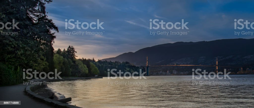 View of Lions Gate Bridge from the Stanley Park Seawall at twilight stock photo